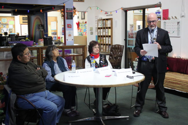 Juneau Schools Superintendent Mark Miller reads his decision in the company of three guests - Marcelo Quinto, Charlotte McConnell and Katherine Hope - who attended Native boarding schools as children. (Photo by Lisa Phu/KTOO)