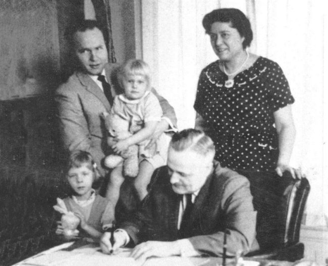 Gov. Bill Egan signs a bill by Rep. Jay Kerttula, holding his daughter Anna, into law. Also pictured, wife  Joyce Kerttula and daughter Beth Kerttula.