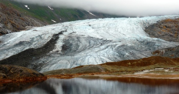 A glacier reflects in a naturally occurring pool of rusty, acidic water at the site of one of the KSM Prospect's planned open-pit mines. (Ed Schoenfeld/ CoastAlaska News).