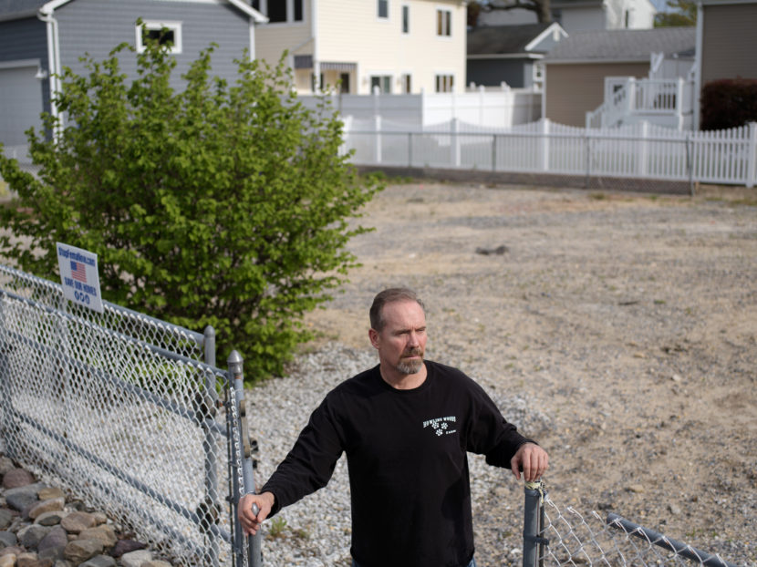 Doug Quinn stands on the empty lot where his house used to be. Bryan Thomas for NPR