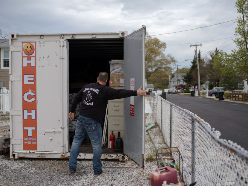 Doug Quinn closes his storage container, on the empty lot of his home destroyed by Superstorm Sandy. Bryan Thomas for NPR