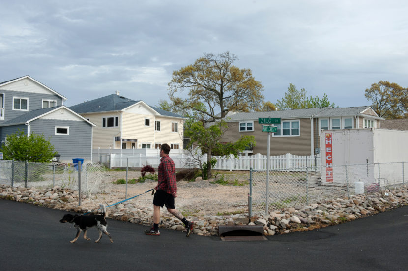Life in the neighborhood continues on around the empty lot where Doug Quinn's house used to stand in Toms River, N.J. Bryan Thomas for NPR