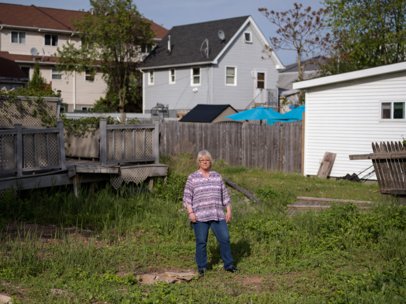 Like many other homeowners, Ann Marie Cianci — standing near her abandoned house on Staten Island, N.Y. — has been unable to move back home. After paying flood insurance for 32 years, she received only $60,000 out of her $250,000 policy. Bryan Thomas for NPR