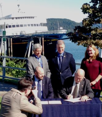 Gov. Bill Walker signs a memorandum of understanding with the Southeast Conference as its President, Gary White, Lt. Gov. Byron Mallott and Transportation Commissioner Marc Luiken watch Thursday at the Auke Bay Ferry Terminal. (Photo by Ed Schoenfeld/ CoastAlaska News)