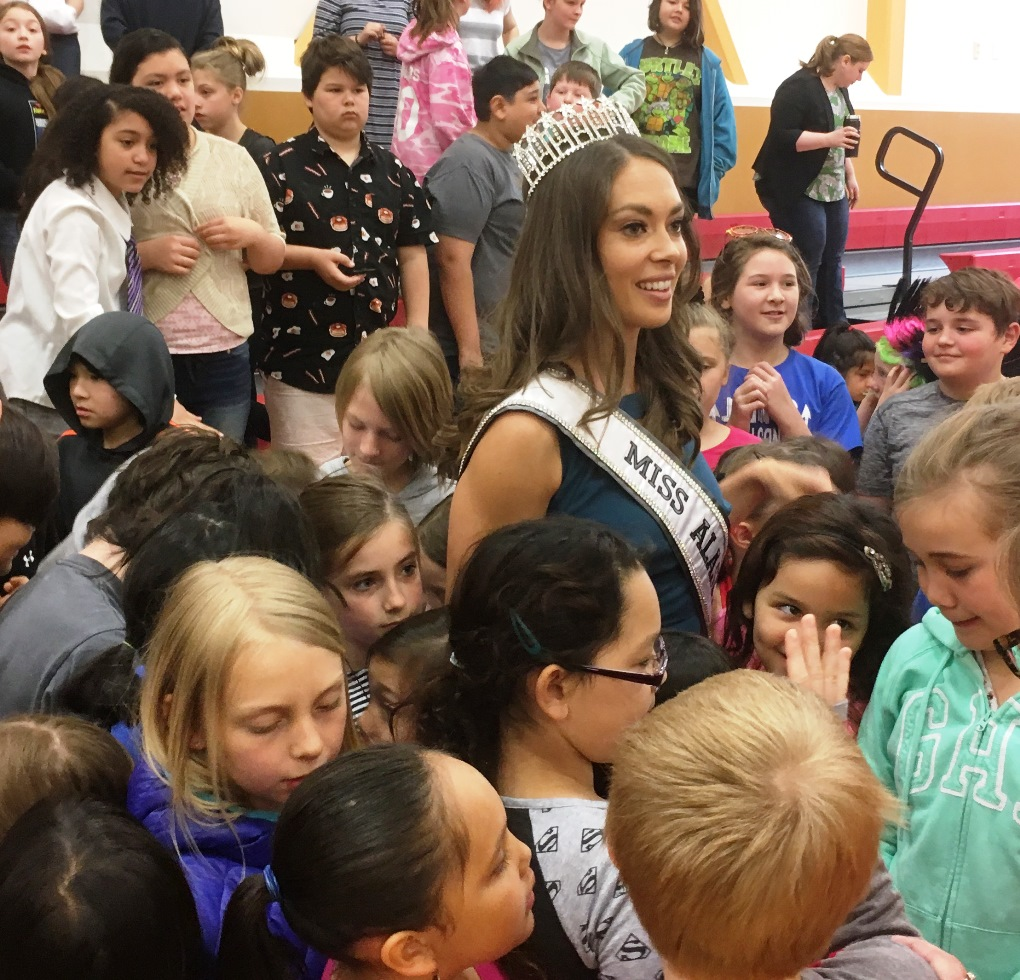 Miss Alaska USA Alyssa London stands for a group photo with students at Fawn Mountain Elementary School. (Photo by Leila Kheiry/KRBD)