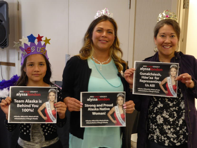 Sierra Flores, left, her mother Serena Hinchman and Raeanna Holmes holds signs at the Miss USA watch party in the Elizabeth Peratrovich Hall in Juneau on Sunday, May 14, 2017. Hinchman and Holmes work for Central Council of the Tlingit and Haida Indian Tribes. of Alaska.