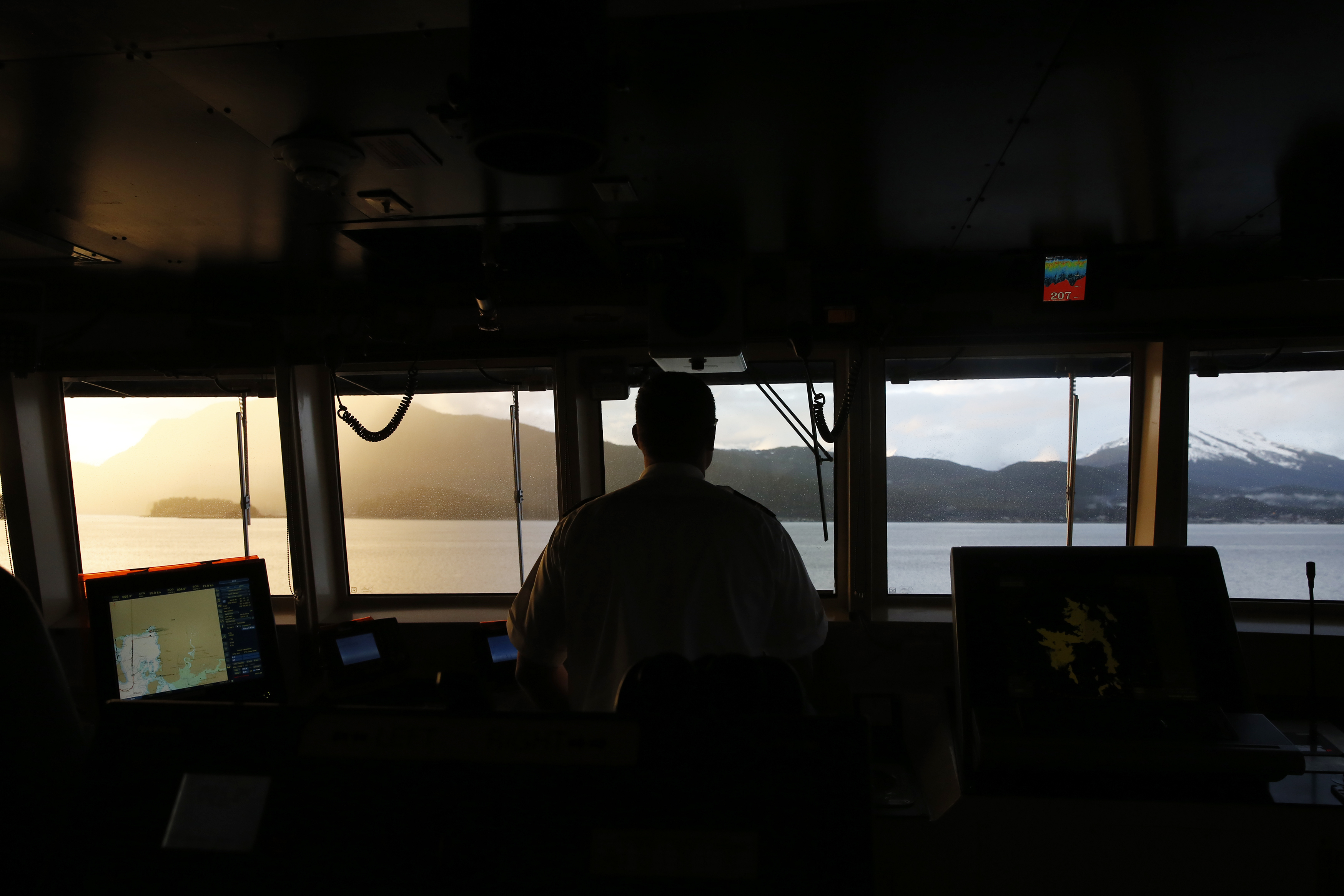 First Mate Aaron Isenhour steers the MV LeConte, a ferry heading from Haines, Alaska, to the state capital, Juneau. (Photo by Elissa Nadworny/NPR)