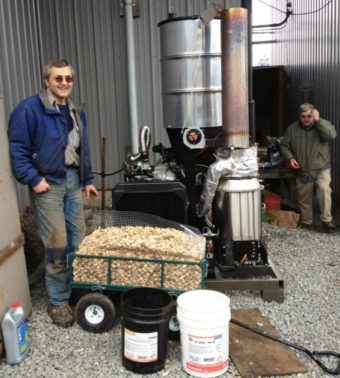 Wes Tyler, left, stands by a new wood gasifier at Icy Straits Lumber in Hoonah. John Hillman of the Hoonah Indian Association is on the right