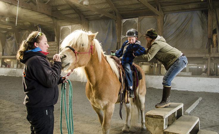 Honnalee Elkan helps a rider off of Higgins as Sarah Milks holds the lead.