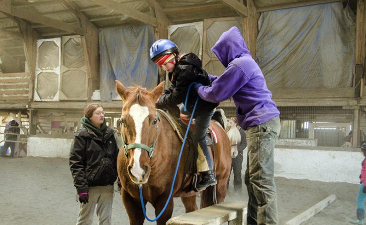 Sonja Hendricksen helps a rider mount her mare Jetta.