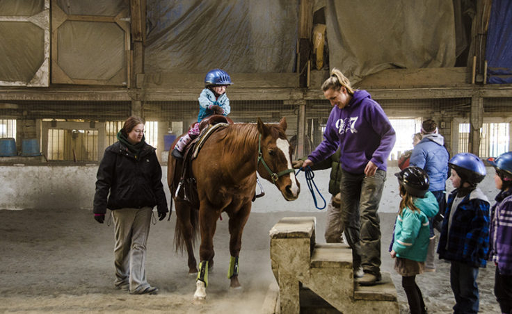 Sonja Henricksen brings Jetta back to the mounting block as Anya Hay keeps an eye on the rider.