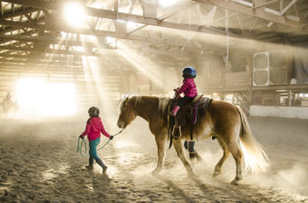 Sunlight streams into the dusty barn as Higgins carries another rider around the arena.