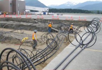 Harri Plumbing and Heating workers install piping in the ground that provides the geothermal ground loop for the airport'€™s heat pump system. There are about 16 miles of piping in the ground. (Photo taken by Airport Construction Assistant, Greg Jerue.)