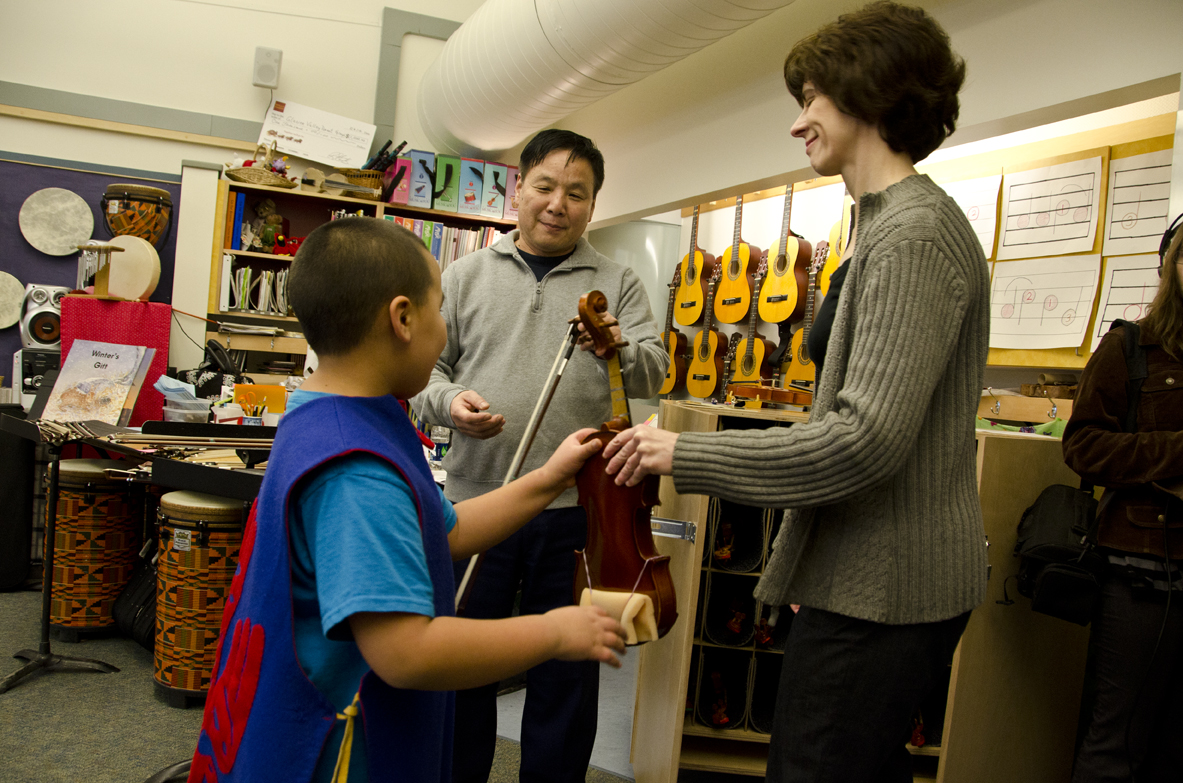 Glacier Valley Elementary music teacher Lorrie Heagy hands a student a violin as violin instructor Guo Hua Xia picks out a bow.