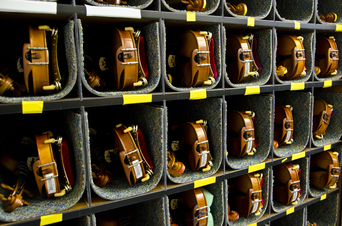 A cabinet of violins in the music classroom.