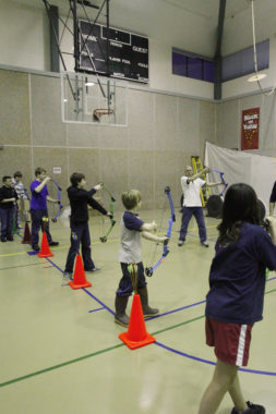 Students learn the proper way to hold an archery bow at Dzantik'i Heeni Middle School gymnasium.
