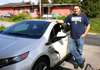 Sitka's lone electric car owner, Michael Mahoney, standing next to his Chevy Volt.