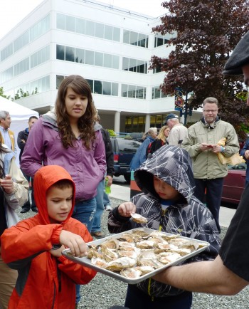 A family samples offerings at 2012's OysterFest. The shellfish came from a Haa Aani-supported oyster farm. (Photo by Ed Schoenfeld/CoastAlaska News)