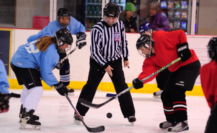Referee Rich Morris drops the puck for Kim Milton (blue) and Mindy Shaw to battle for during the 10th Annual Jamboree women's hockey tournament at Treadwell Ice Arena.