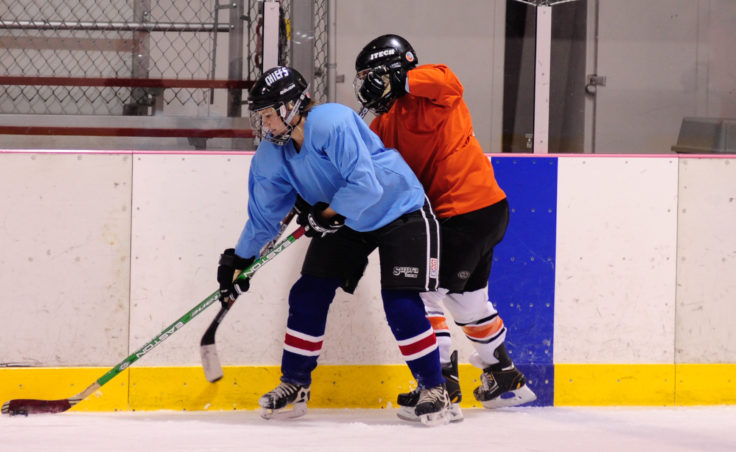 Caroline Schultz keeps Jill Weitz at bay while maintaining control of the puck along the boards during the 10th Annual Jamboree women's hockey tournament at Treadwell Ice Arena.