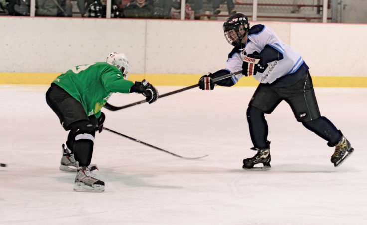 Thomas McKenzie pushes a shot past defenseman Mike Cooney in a game decided by a single goal in a 1-0 Tier B Alaska Airlines victory.