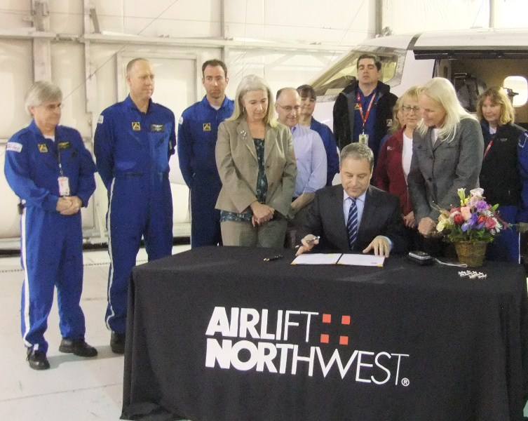 Gov. Sean Parnell signed SB 159 at the Airlift Northwest hangar in Juneau. Rep. Cathy Munoz is left. Airlift Northwest director Chris Martin is on the right. (Photo by Rosemarie Alexander/KTOO)