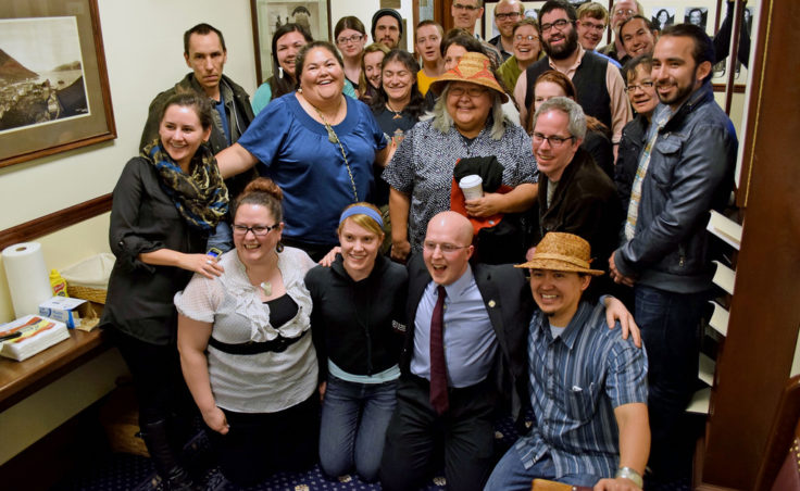 Rep. Jonathan Kreiss-Tomkins (front row, second from the right) poses with supporters of House Bill 216, which had passed moments earlier. The legislation, which he introduced, makes 20 Alaska Native languages official state languages alongside English. (Photo by Skip Gray/Gavel Alaska)