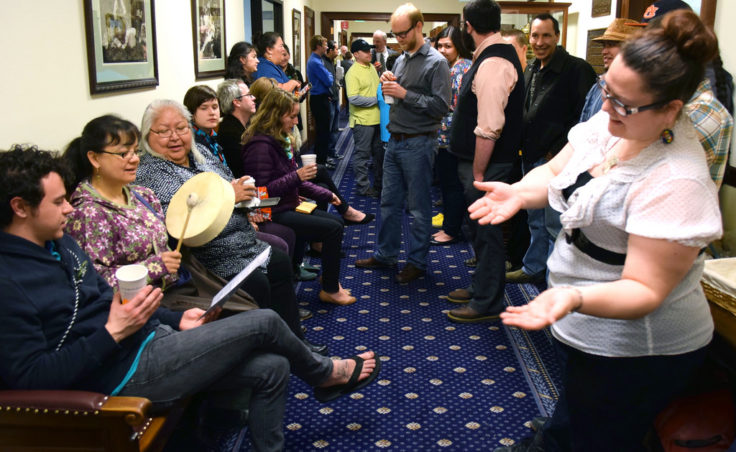 Irene Lampe drums while Ricky Tagabon (to her right) and Della Cheney (to her left) sing while Jessica Dominy dances in traditional Tlingit style in the second floor hallway of the Alaska State Capitol, April 21, 2014. They were a few of the one hundred or so supporters of House Bill 216 that gathered on April 21, 2014, and stayed until 3am the next day waiting for the Senate to pass the bill that makes 20 Alaska Native languages official state languages alongside English. (Photo by Skip Gray/Gavel Alaska)