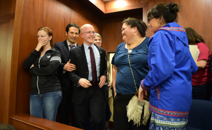 In the Senate gallery, Marian Call, Rep. Neal Foster, Rep. Jonathan Kreiss-Tomkins, Liz Medicine Crow and Rep. Charisse Millett (left to right) react seconds after passage of his legislation making 20 Alaska Native languages official state languages alongside English. The vote took place at 3am, April 21, 2014 after an all-day vigil by about one hundred supporters. (Photo by Skip Gray/Gavel Alaska)