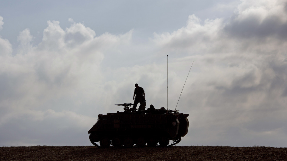 An Israeli soldier stands on a military vehicle near Gaza early Tuesday, when a cease-fire was meant to take effect. The deal hasn't been embraced by all of Hamas. Ariel Schalit/AP