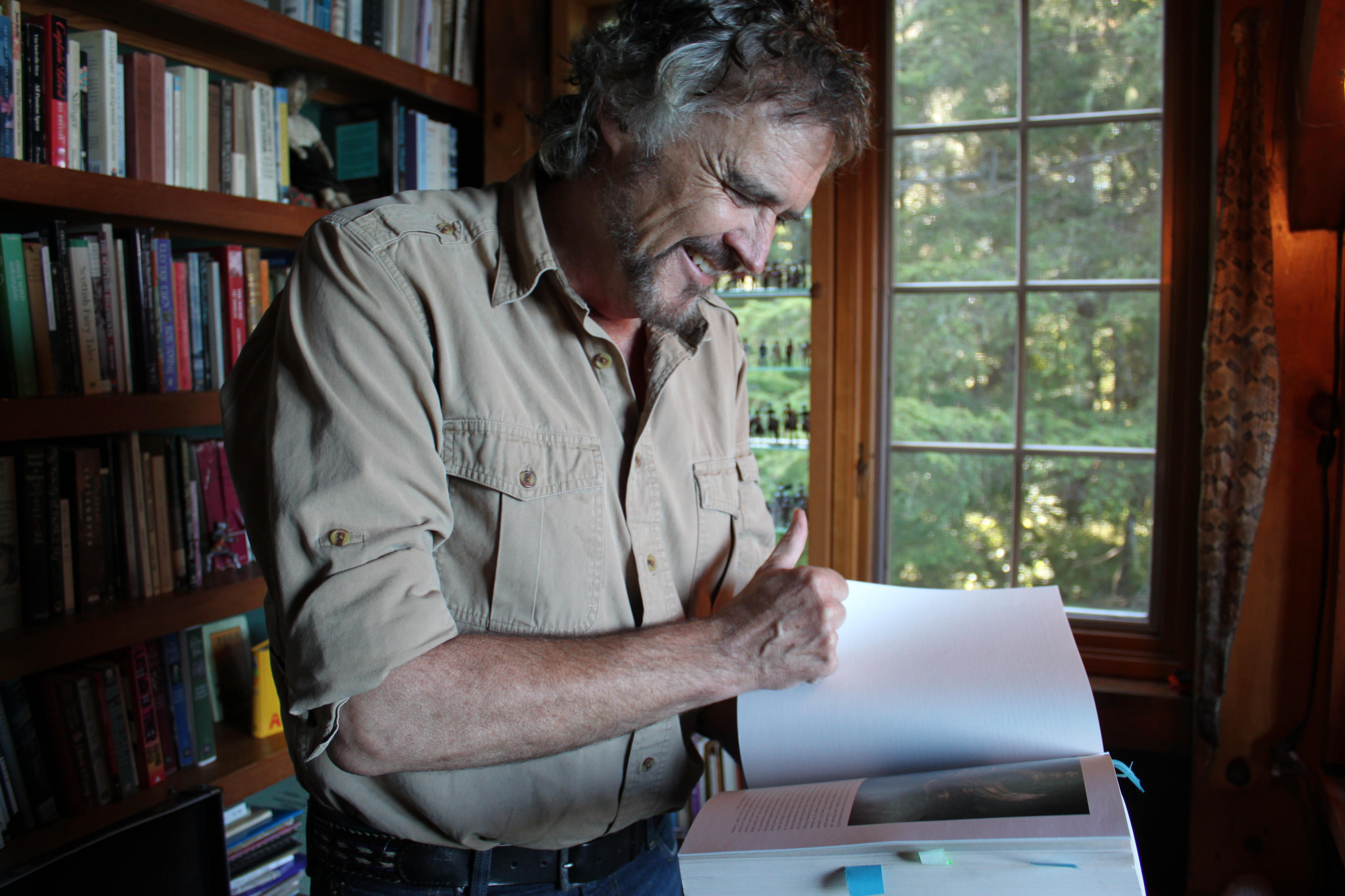 """At home a day after Dick Dauenhauer died, Juneau playwright Dave Hunsaker flips through his copy of """"Anóoshi Lingít Aaní Ká/Russians in Tlingit America: The Battles of Sitka, 1802 and 1804."""" (Photo by Lisa Phu/KTOO)"""