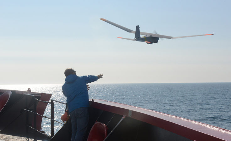 John Ferguson, an Unmanned Aircraft System operator for AeroVironment, releases a Puma All Environment UAS from the deck of the Coast Guard Cutter Healy during an exercise in the Arctic Aug. 23, 2014. The Puma is a small UAS designed for land and maritime operations. (Coast Guard photo by Petty Officer 1st Class Shawn Eggert)