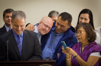 Representative Jonathan Kreiss-Tomkins of Sitka, Nome's Bernadette Yaayuk Alvanna-Stimpfle, and others look on as Gov. Sean Parnell signs the bill into law. (Photo by Matthew F. Smith/KNOM)