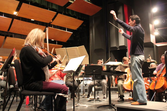 Conductor Troy Quinn leads the Juneau Symphony during rehearsal at the Juneau-Douglas High School auditorium. (Photo by Lisa Phu/KTOO)