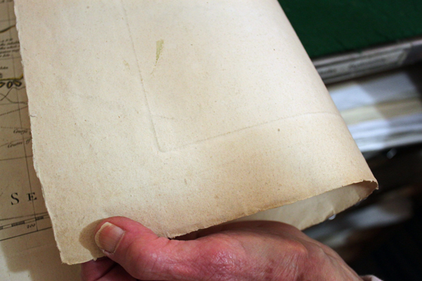 Dee Longenbaugh shows a map's plate mark, the indentation left from an old printing press. It's a sign of an antique map's authenticity. (Photo by Kayla Desroches/KTOO)