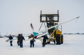 A team of responders transporting the damaged Cessna 185 after it landed at Nome's City Field on Thursday afternoon. (Photo: Francesca Fenzi/KNOM)