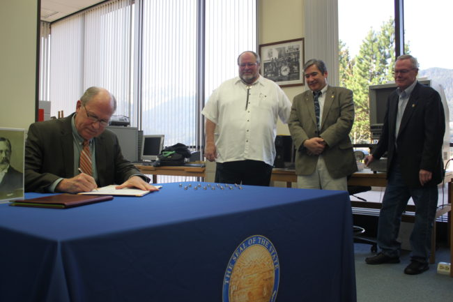 Gov. Bill Walker signs the bill Tuesday morning as Juneau Mayor Merrill Sanford, Rep. Sam Kito III and Sen. Dennis Egan look on. (Photo by Lisa Phu/KTOO)