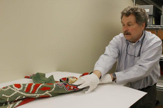 Chuck Smythe unrolls the tunic from storage. (Photo by Elizabeth Jenkins/KTOO)