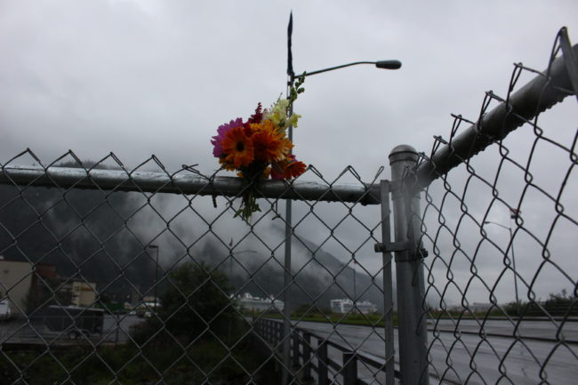 Flowers stuck in the fence above the bridge as memorial. (Photo by Elizabeth Jenkins/KTOO)