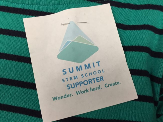 Advocates for the Summit STEM School wore these pinned to their shirts. Alberta Jones,  a member of the school's formation committee, says the logo is incomplete. (Photo by Lisa Phu/KTOO)