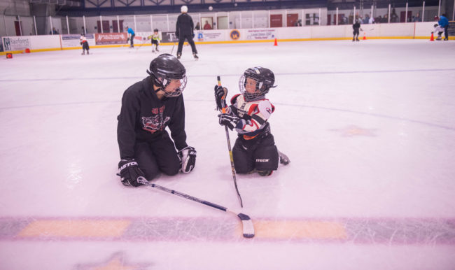 Juneau Bantam standout Greyson Liebelt works one-on-one with Jacob King who is getting his first taste of hockey at Treadwell Ice Arena. (Photo by Steve Quinn)