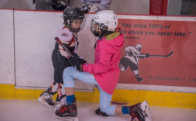 Kyla Bentz helps Violet Young get acquainted with the ice during JDIA's Learn to Play afternoon at Treadwell Ice Arena. (Photo by Steve Quinn)