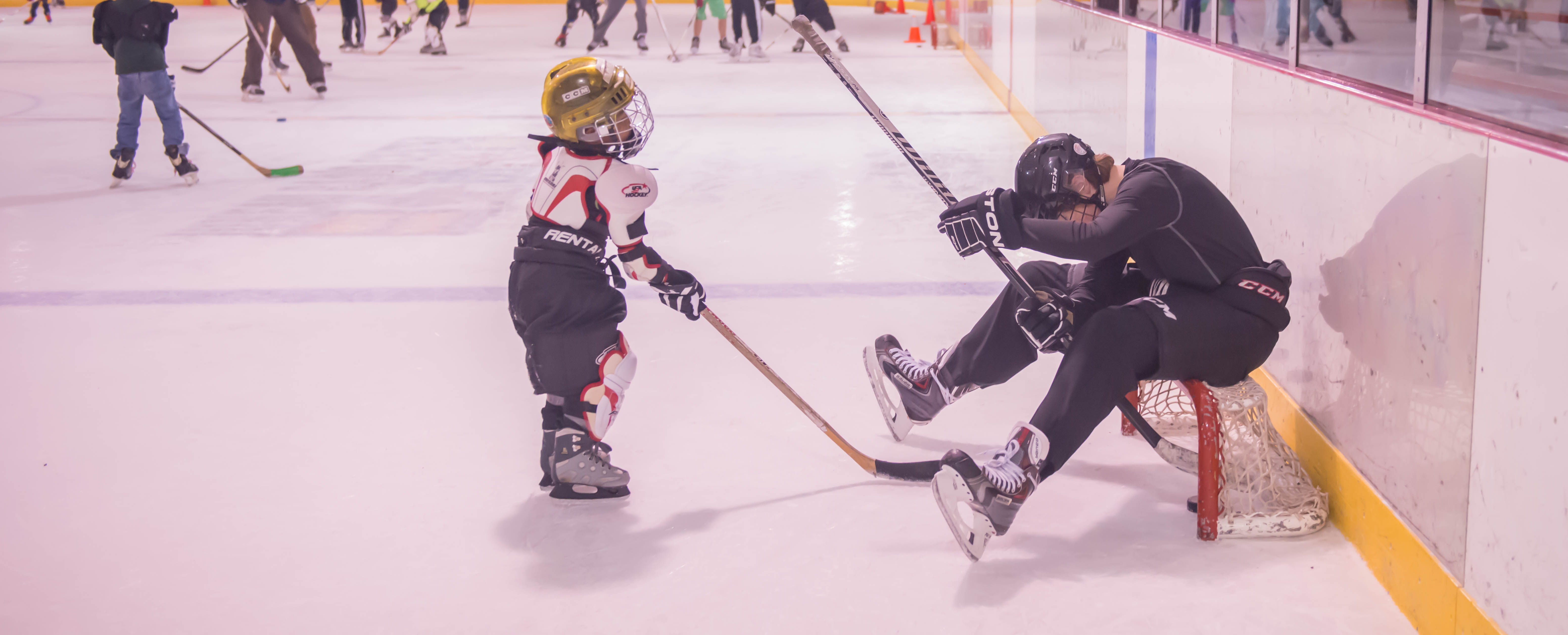 Owen Squires (right) looks for the puck shot by Joshua Mazon during JDIA's Learn to Play afternoon at Treadwell Ice Arena. (Photo by Steve Quinn)