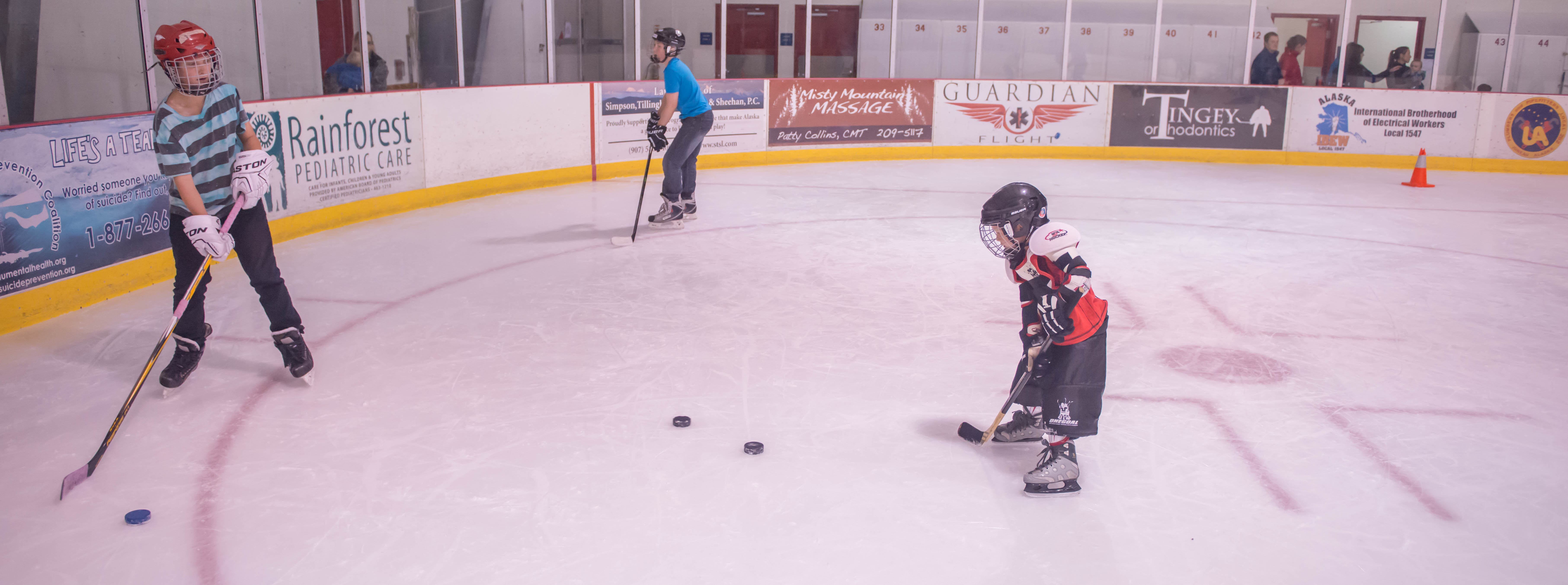 Jack York works with Braedon Pearson during JDIA's Learn to Play afternoon at Treadwell Ice Arena. (Photo by Steve Quinn)
