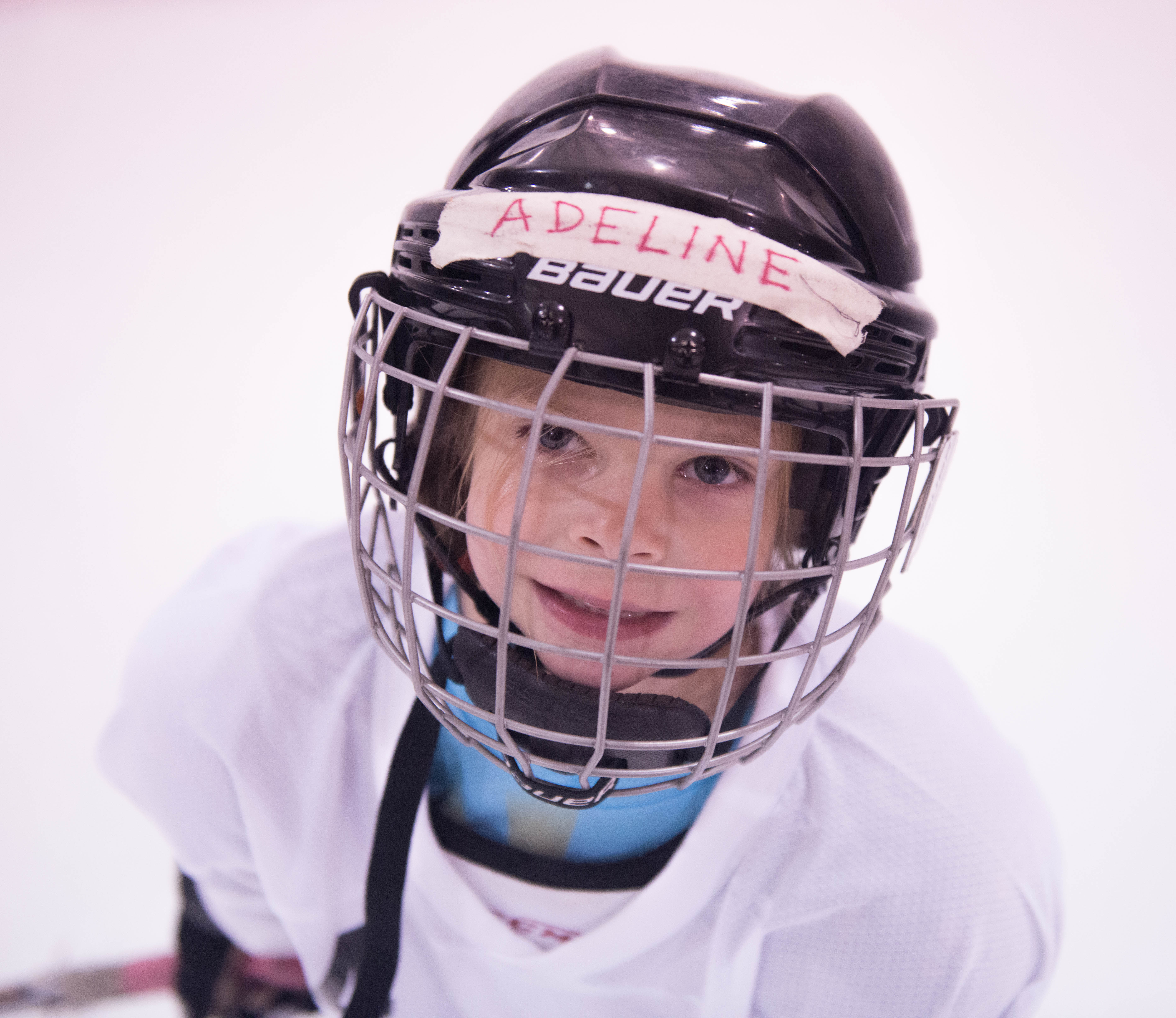 Adeline Janson flashes a quick smile through her hockey cage while skates around Treadwell Ice Arena at JDIA's Learn to Play afternoon. (Photo by Steve Quinn)
