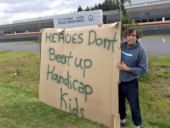 Kodiak resident Brent Watkins silently demonstrated outside the Kodiak Police station Friday, Sept. 18, 2015, two days after a friend with learning disabilities was contacted by three Kodiak police officers. (Photo by Jay Barrett/KMXT )
