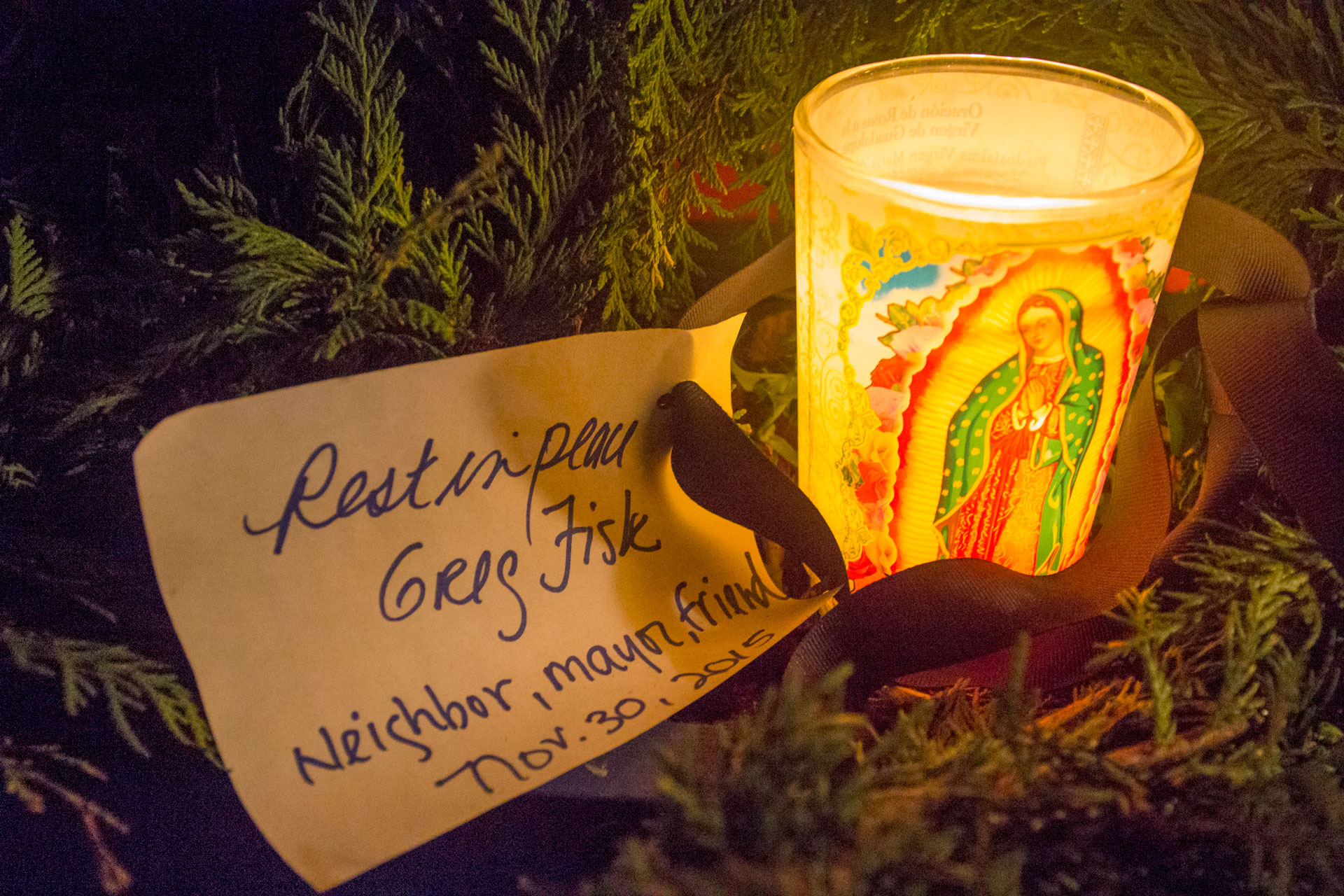 """A candle and a note reading """"Rest in peace Greg Fisk. Neighbor, mayor, friend. Nov. 30, 2015"""" outside a neighbor's house on Kennedy St. Monday evening. (Photo by Mikko Wilson/KTOO)"""