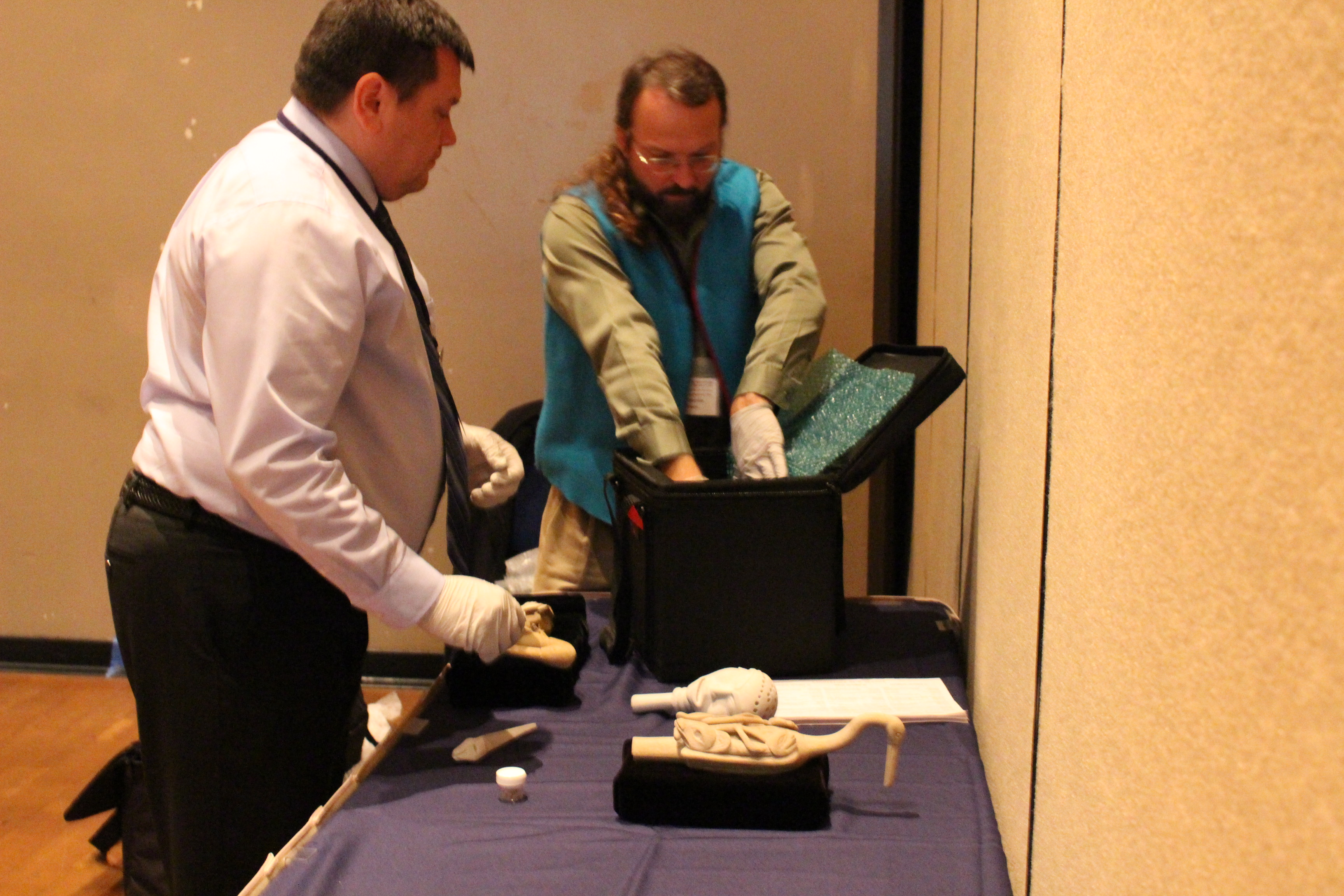 Eric Hollinger and Robert Starbard put the replicas away. KTOO obtained permission to photograph the objects. (Photo by Elizabeth Jenkins/KTOO)