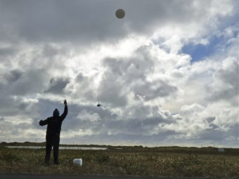 William Wells releases a weather balloon on Alaska's St. Paul Island. (Photo by John Ryan/KUCB)