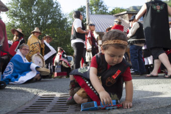 Jeffrey Mark, Tsimshian from Anchorage, plays with train while waiting for his group's turn to march during a processional and grand entrance on Wednesday, June 8, 2016, near Juneau, Alaska. Celebration is a biennial festival of Tlingit, Haida and Tsimshian tribal members put on by the Sealaska Heritage Institute. (Photo by Rashah McChesney/KTOO)